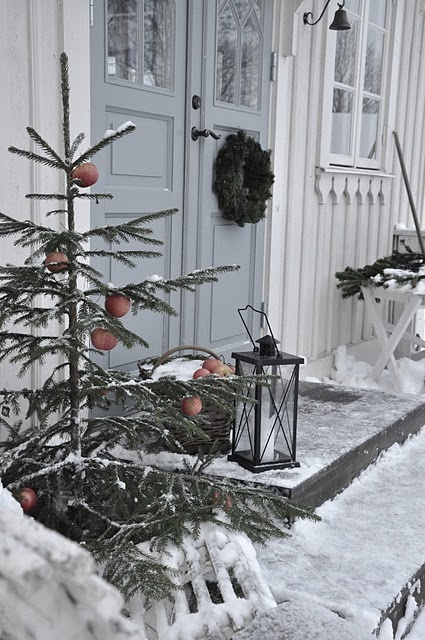 a Christmas tree with apples, a candle lantern and a fir branch wreath on the door for a natural feel in the porch