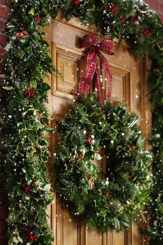 a lush greenery and berry garland framing the door and a matching wreath with a bow on top for a gorgeous Christmas front porch