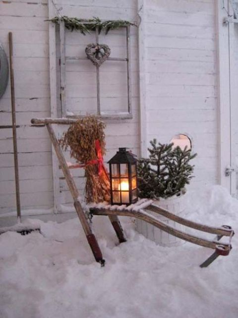 a rustic decoration - a lounger with dried herbs, a lantern, fir branches in a pot and a window frame with a vine heart for your backyard or front one