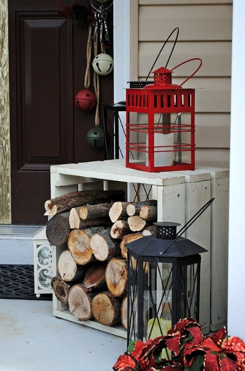 a crate with firewood, oversized candle lanterns and bright bells hanging on the door for a festive and rustic feel