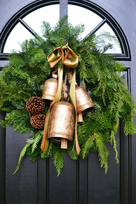 A Chic Christmas Wreath Of Fir Branches With Vintage Bells, Pinecones And Rope Is A Pretty Vintage Holiday Decor Idea