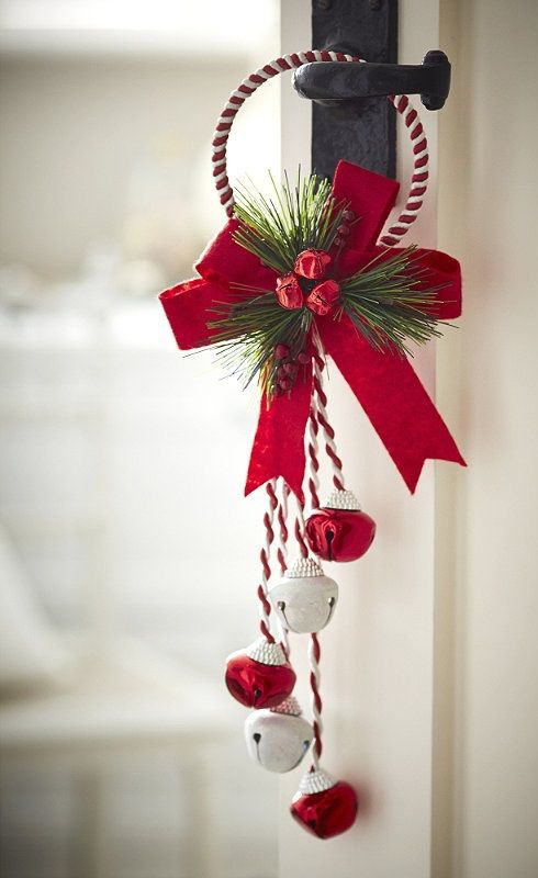 a bright Christmas door hanging of red and white bells, yarn, a red bow, fir twigs and berries is a cool decoration