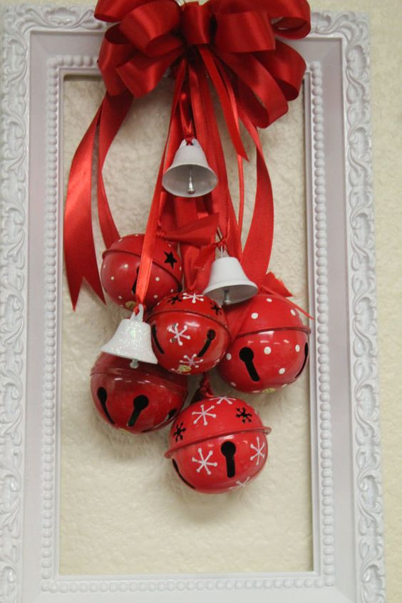 A Bold Christmas Decoration Of A White Frame, Red Christmas Bells And Mini White Ones, A Red Bow