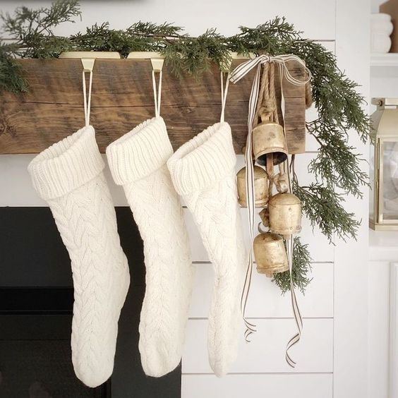 A Pretty Christmas Mantel With White Stockings, Vintage Bells, Striped Ribbons And A Fir Garland