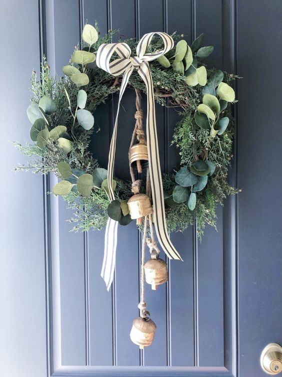 A Greenery And Foliage Christmas Wreath With A Striped Bow And Large Vintage Bells Is A Lovely And Chic Decoration