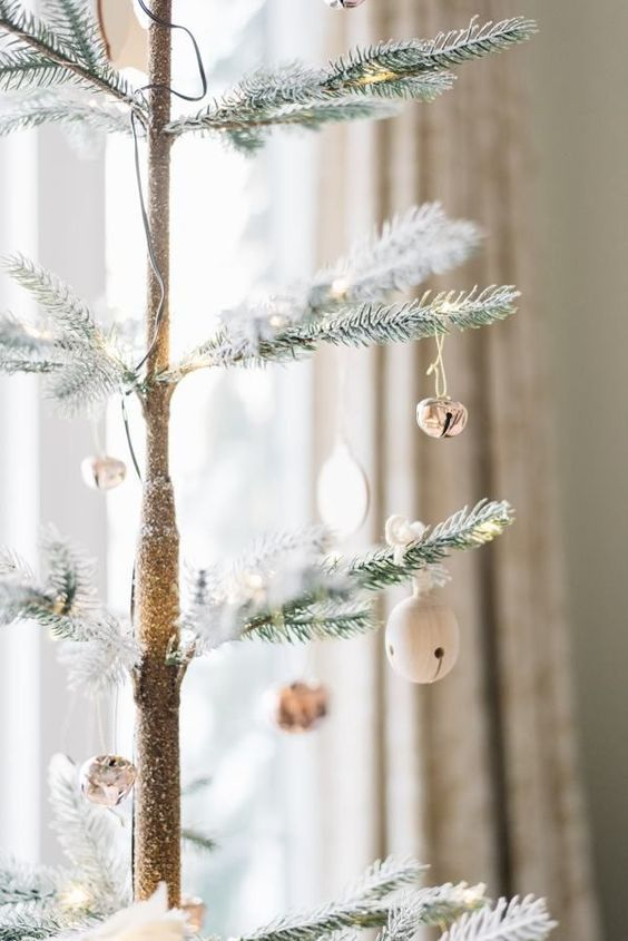 A Christmas Tree Decorated With White And Silver Bell Ornaments, They Bring A Shiny And Cool Touch To The Tree