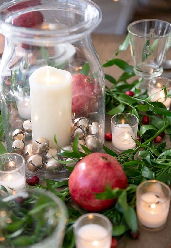 A Natural Christmas Centerpiece Of Greenery, Berries, Pomegranates, Candles And A Glass Jar With Mini Bells And Candles