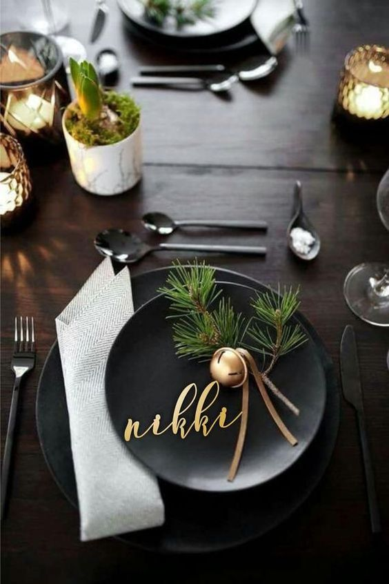 Black Plates, A Neutral Napkin, A Gold Bell With Leather Cords And Fir Twigs For A Modern Christmas Place Setting
