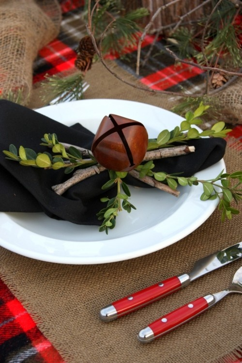 A Natural Christmas Place Setting With A Black Napkin Accented With Sticks, Greenery And An Oversized Bell For A Rustic Christmas Tablescape