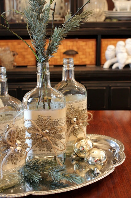 A Vintage Rustic Christmas Centerpiece Of A Silver Tray With Fir Twigs And Silver Ornaments, Bottles With Snowflakes And Silver Bells And Fir Twigs In Them
