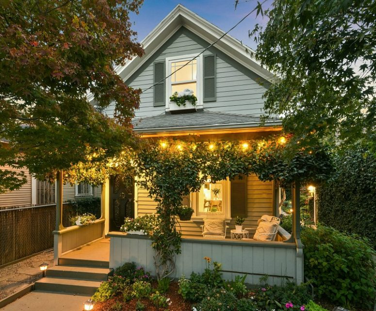 This small and cozy farmhouse is wrapped in greenery and blooms and looks very welcoming and cool